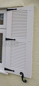 white louvre shutter with decorative hinges