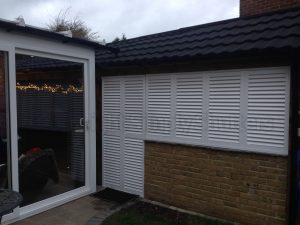 white louvre shutters fitted over a window