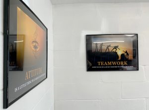 two framed motivational posters on white wall