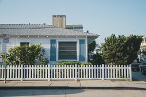 House with blue shutters and white picket fence