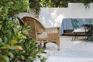 wicker chair in front of bushes in walled outdoor area