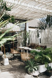 covered garden area with wicker chairs and tropical plants
