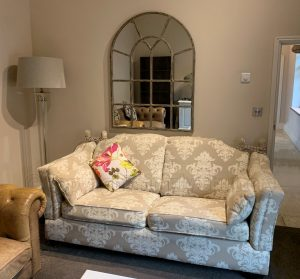 sofa with mirror and lamp in background